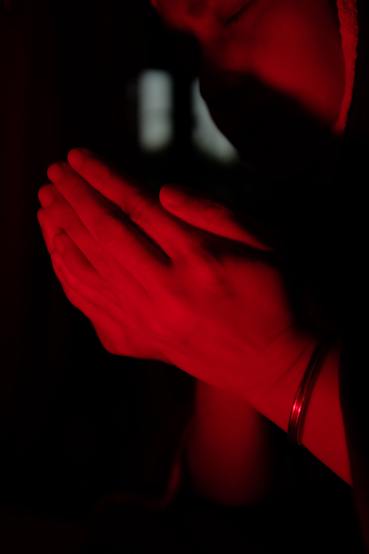 Hands together in prayer under a red light