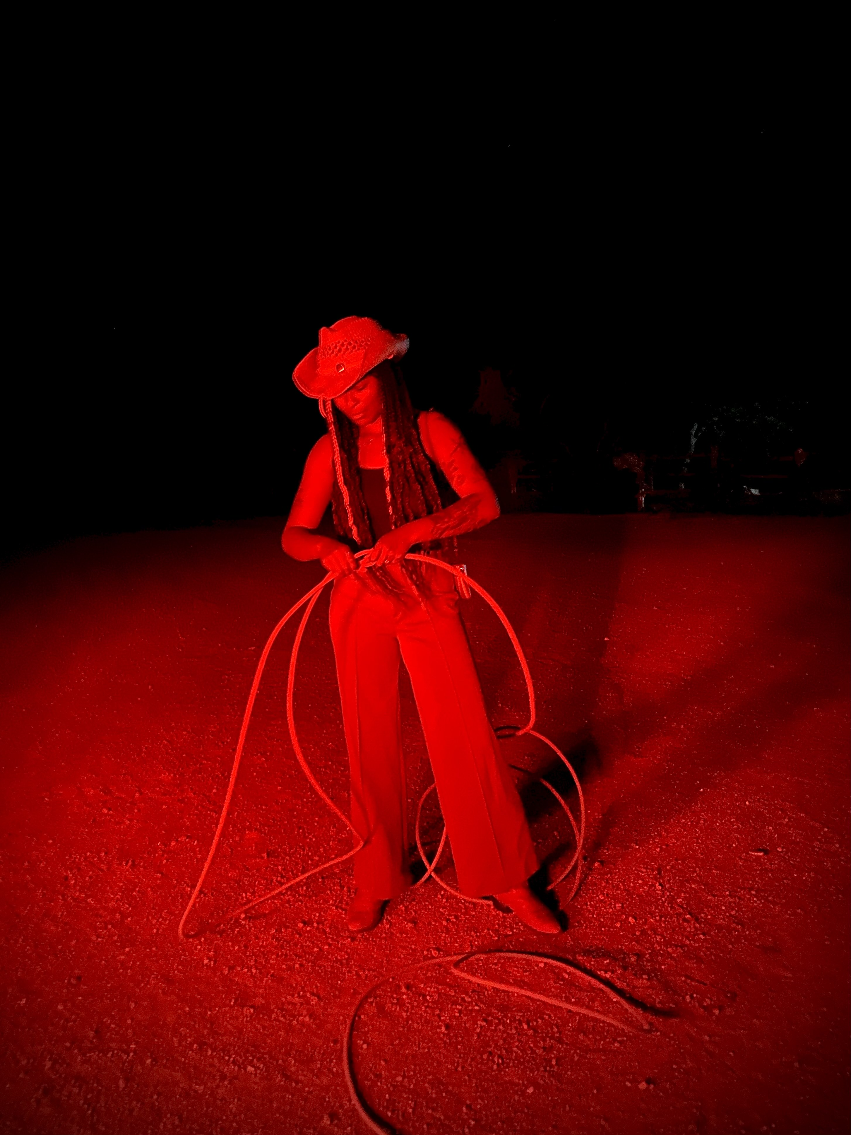 Woman putting together a lasso outside under a red light.
