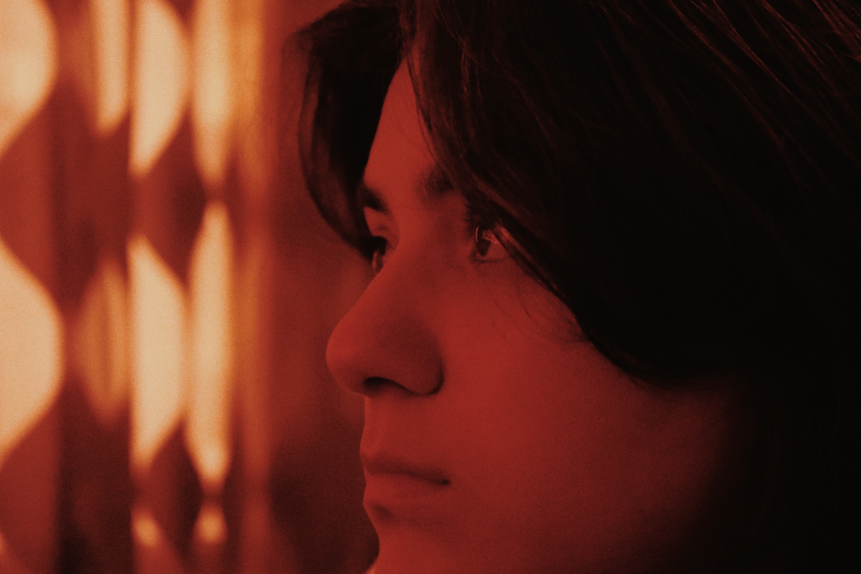 close up of a woman's face with an orange light.