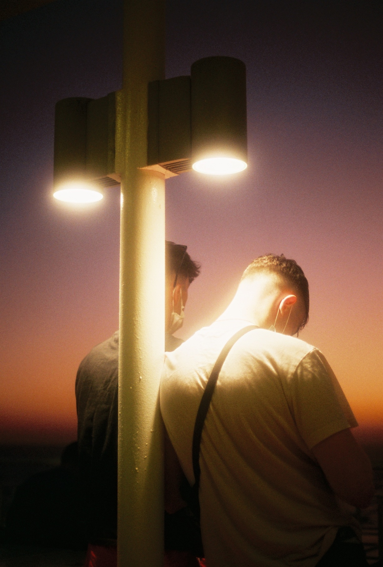 Two men watch the sunset standing against a street lamp