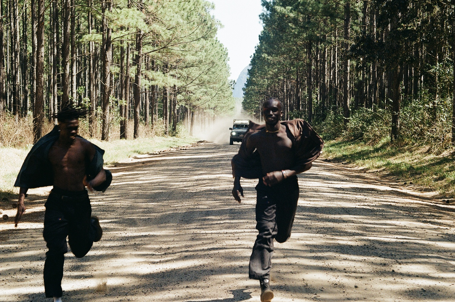 Two boys running in front of a car along a road lined with trees.