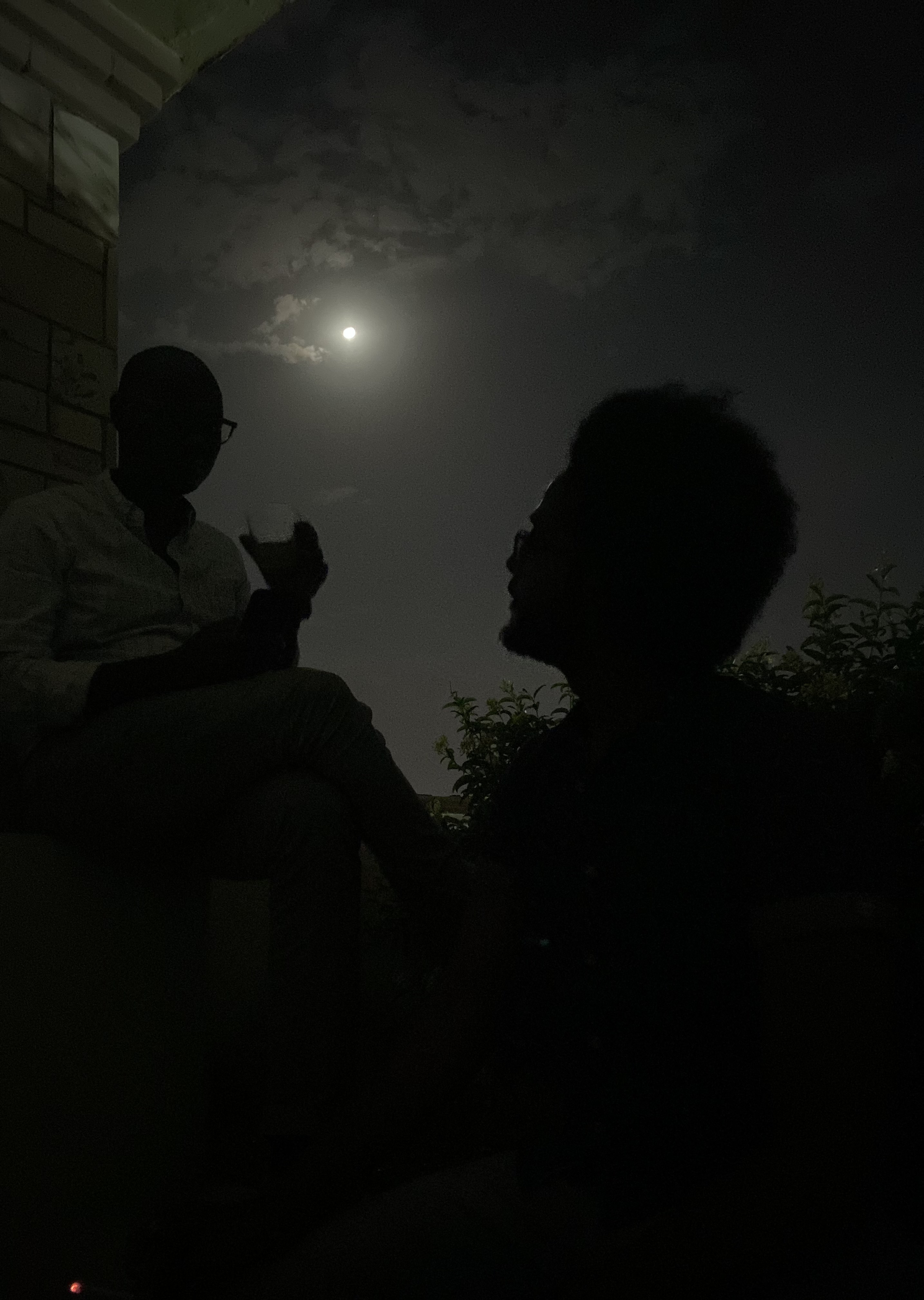 Two people talk under the moonlight at night.