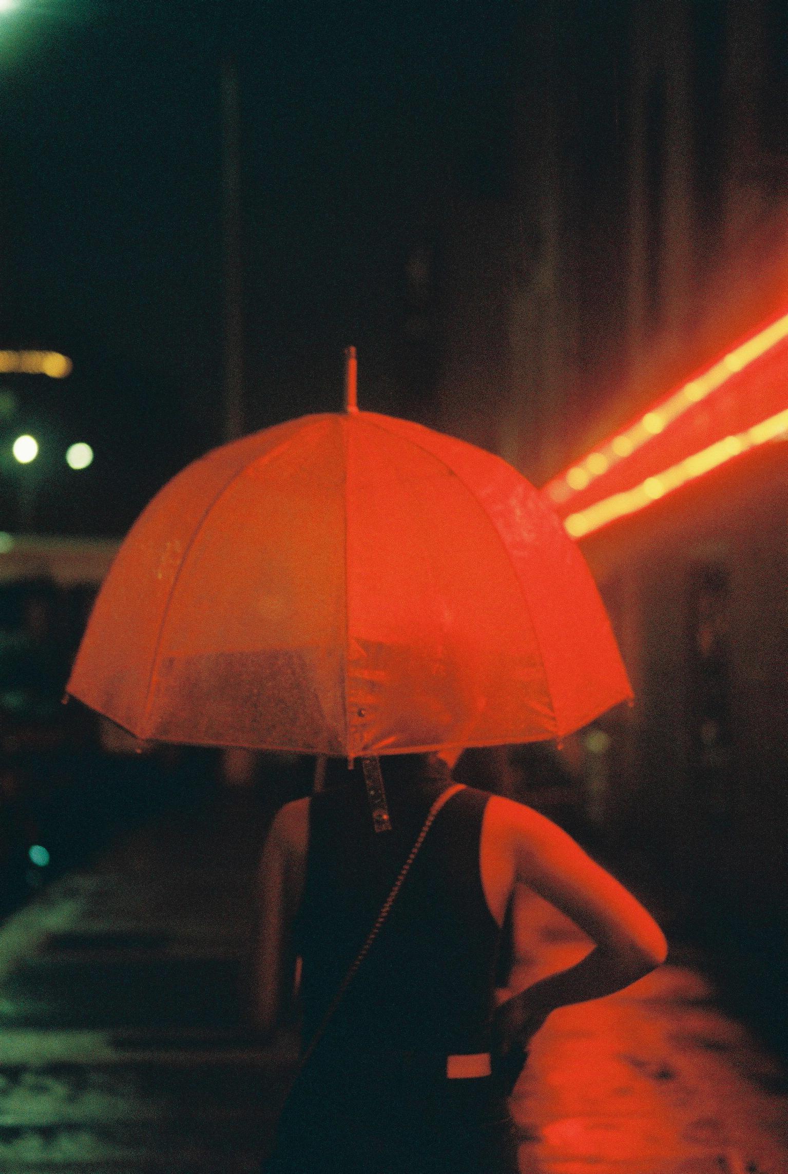 an umbrella lit up by a red neon light