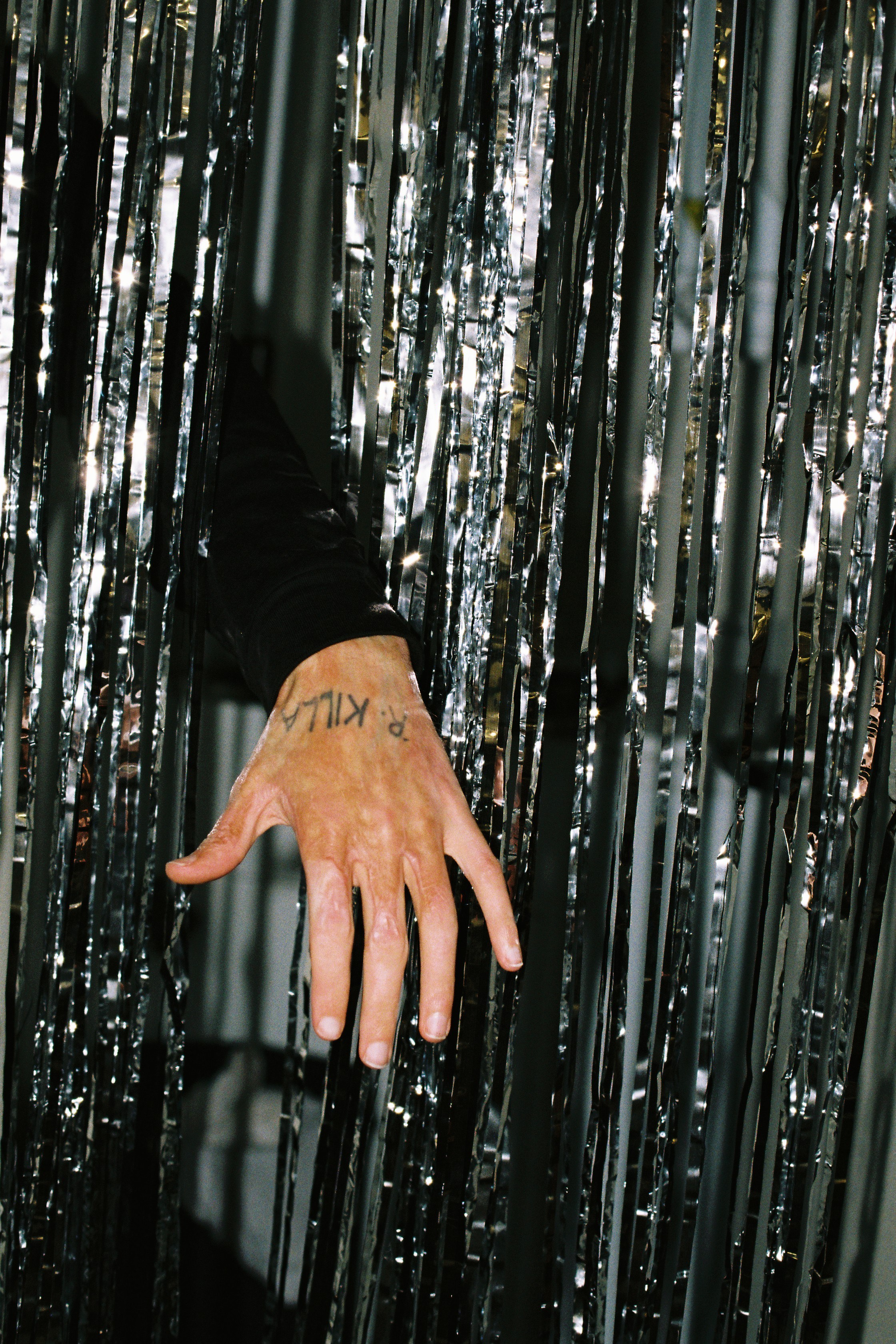 a man's hand with burn marks and an 'R. KILLA' tattoo appearing from silver streamers