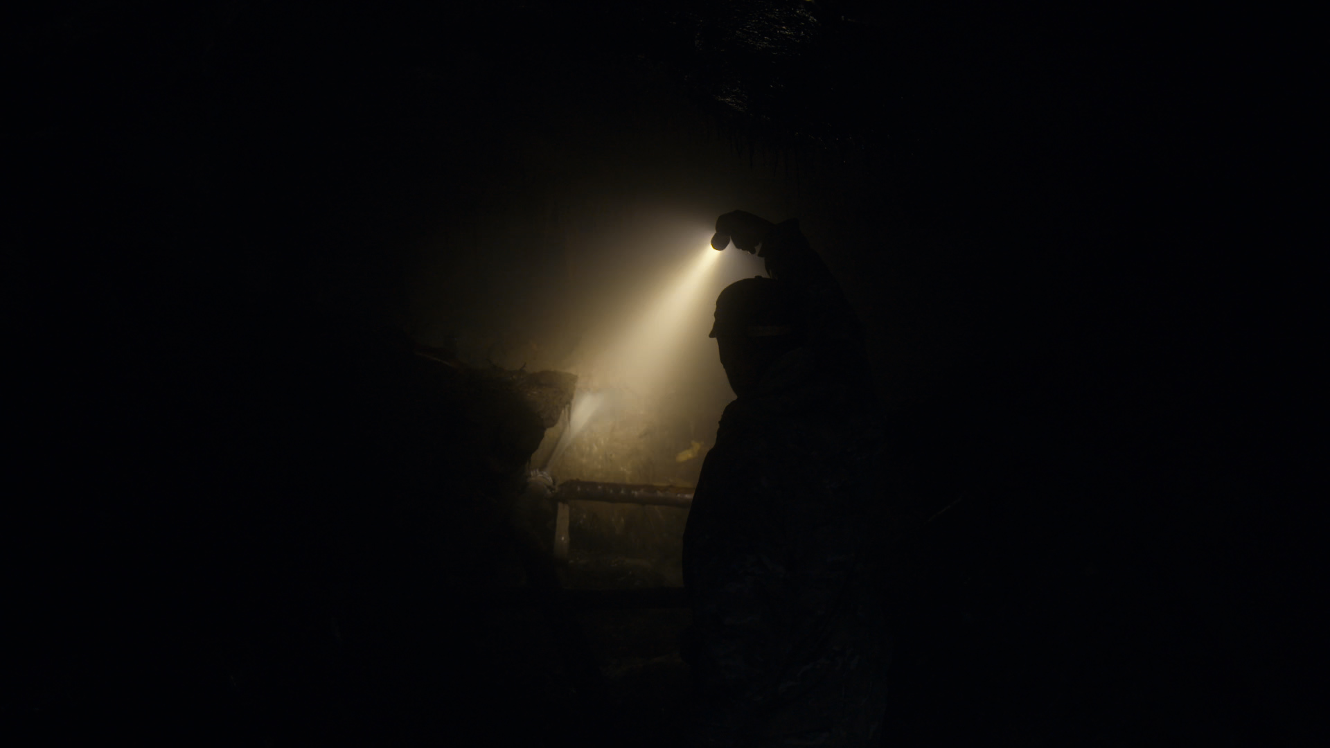 Lelaki menyalakan senter di dalam terowongan