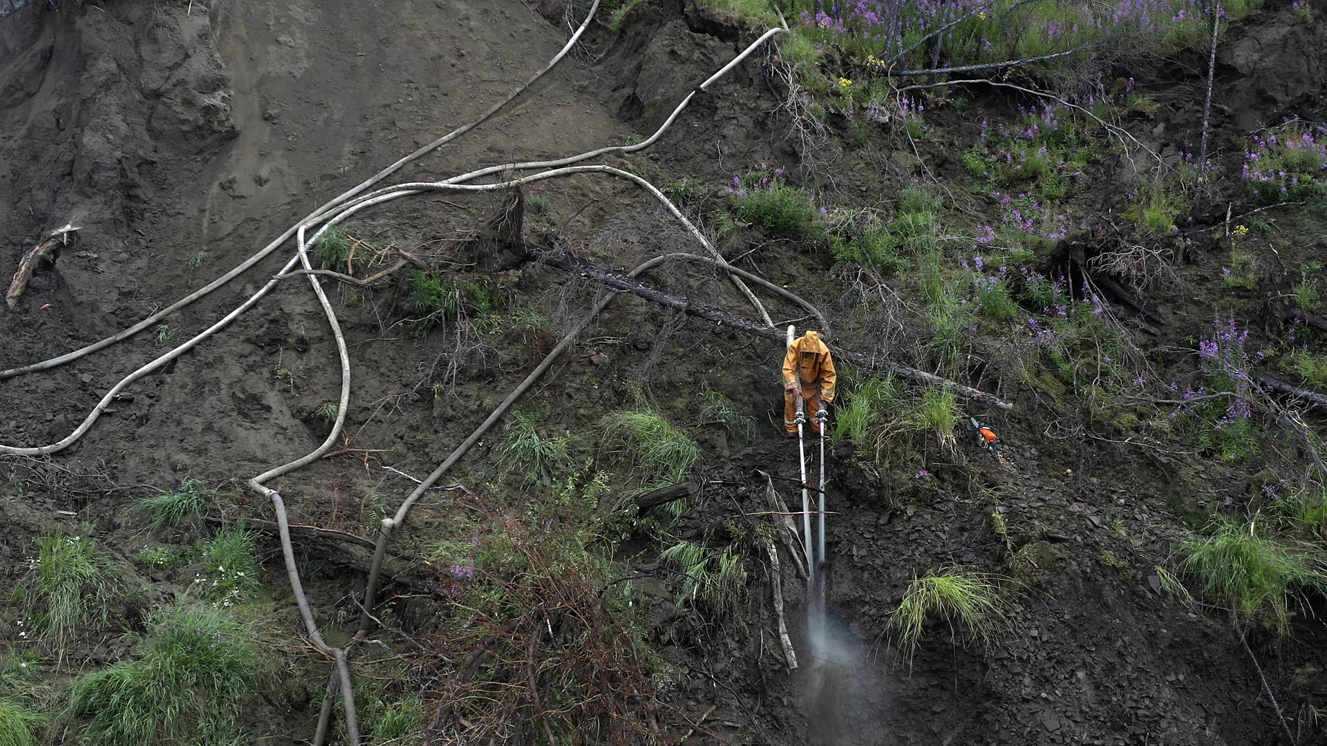 Pemburu menyemprot tanah untuk mencari gading yang terkubur.