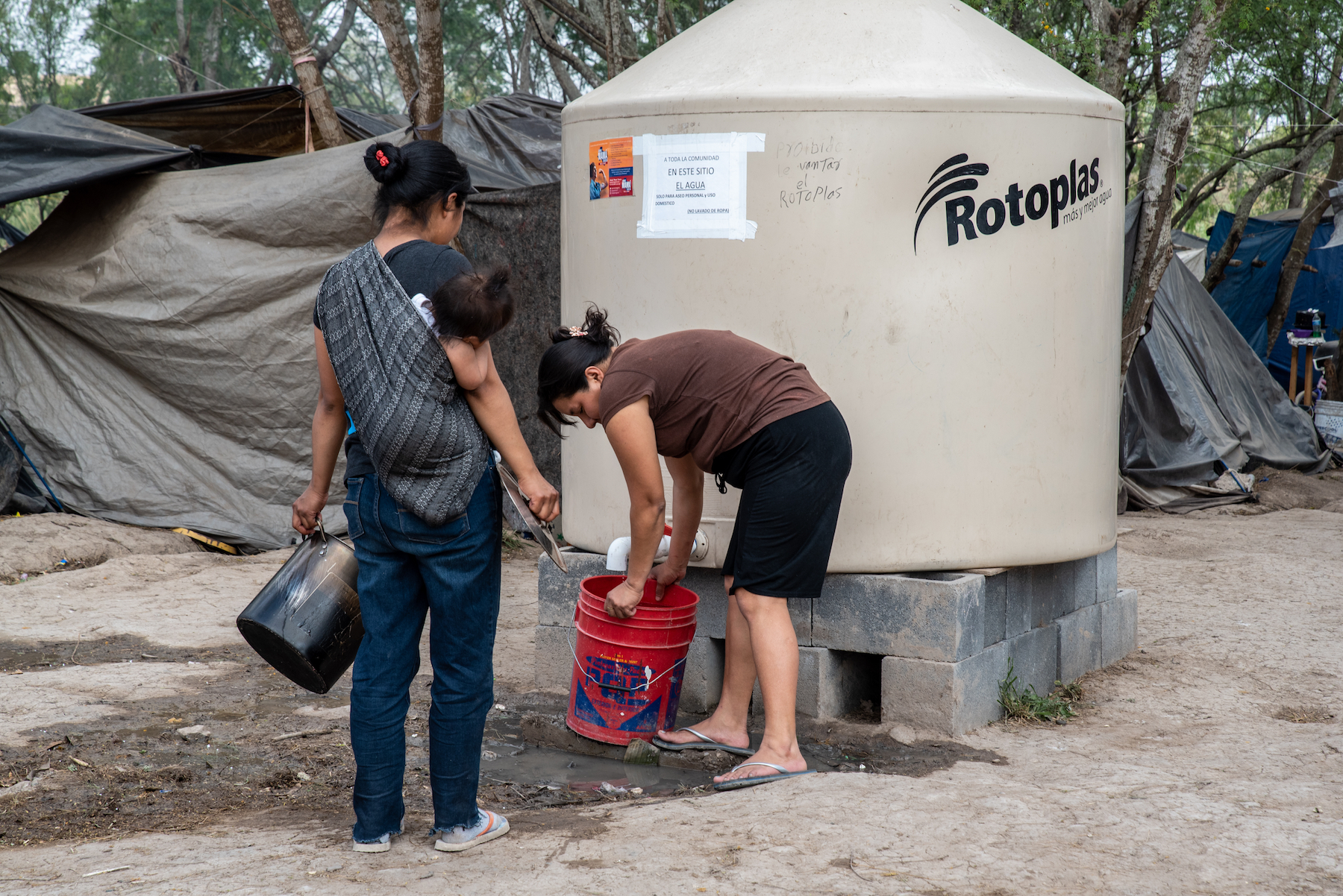 Women pour clean water into a bucket at the camp on March 2. Photo: Sergio Flores/VICE News.