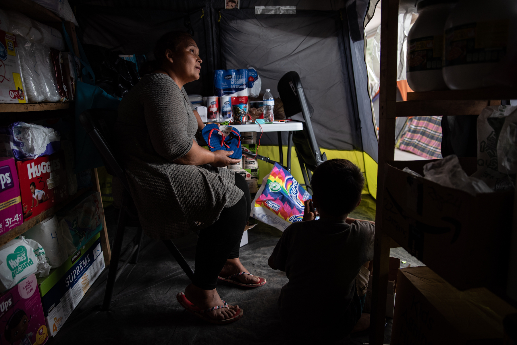 Roxana de Castro sits inside a supply tent while listening to a request from a fellow migrant. Photo: Sergio Flores/VICE News.
