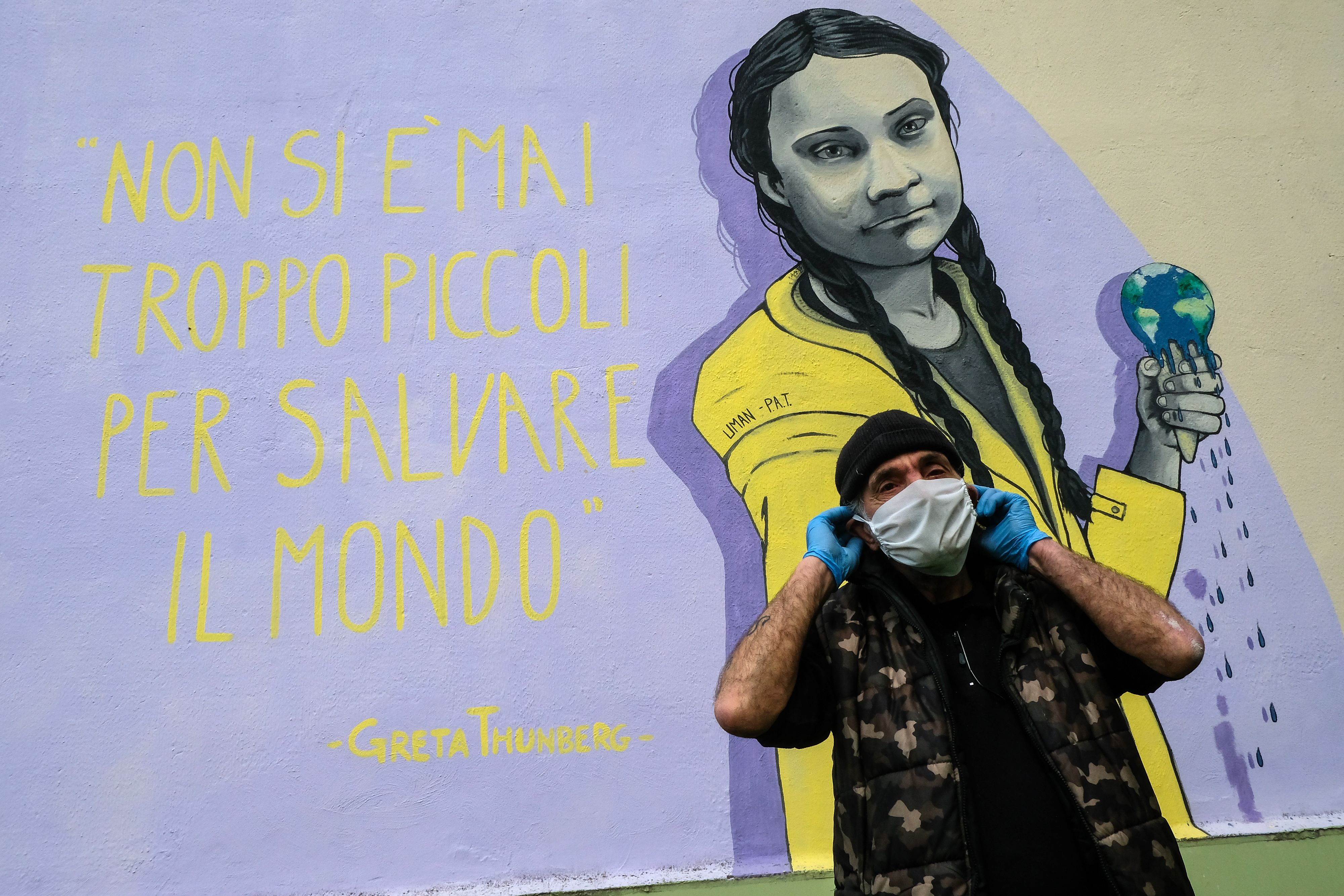 A man in a face mask stands next to an Italian mural of Greta Thunberg