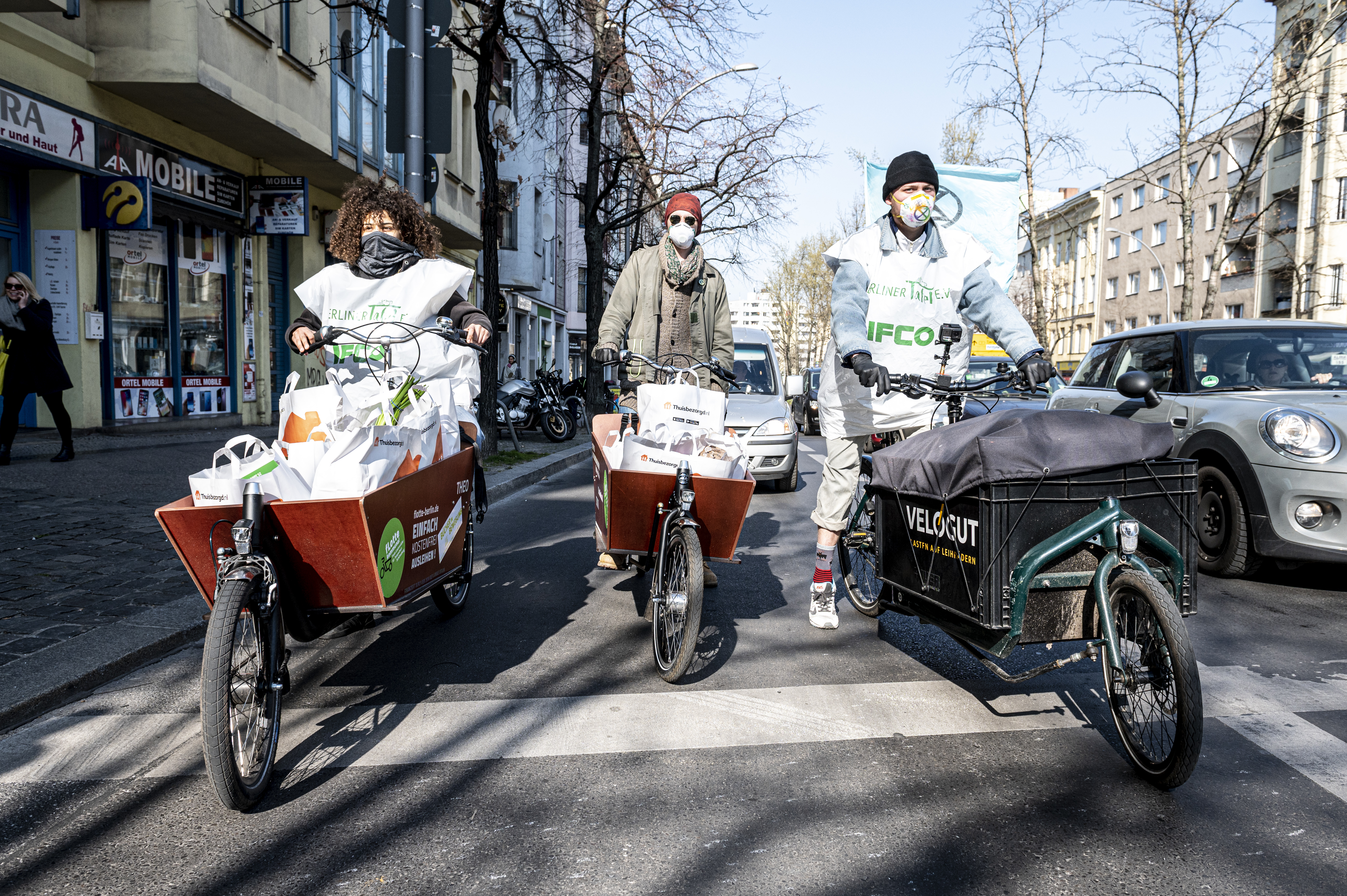 A trio of people on bikes pushing carts full of bags of food while wearing facemasks.