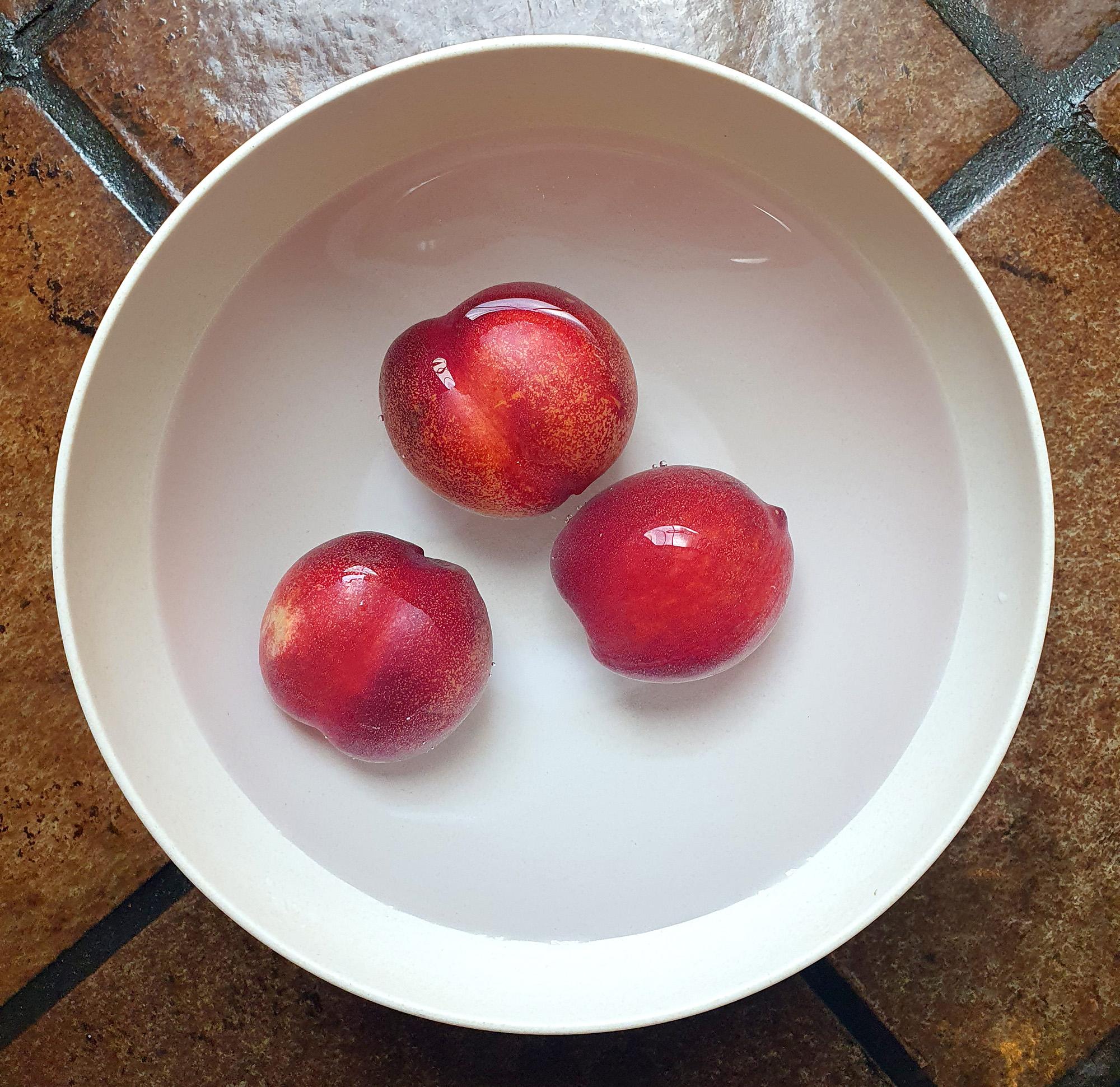 Tiga buah nektarin direndam dalam larutan baking soda. Foto oleh penulis.